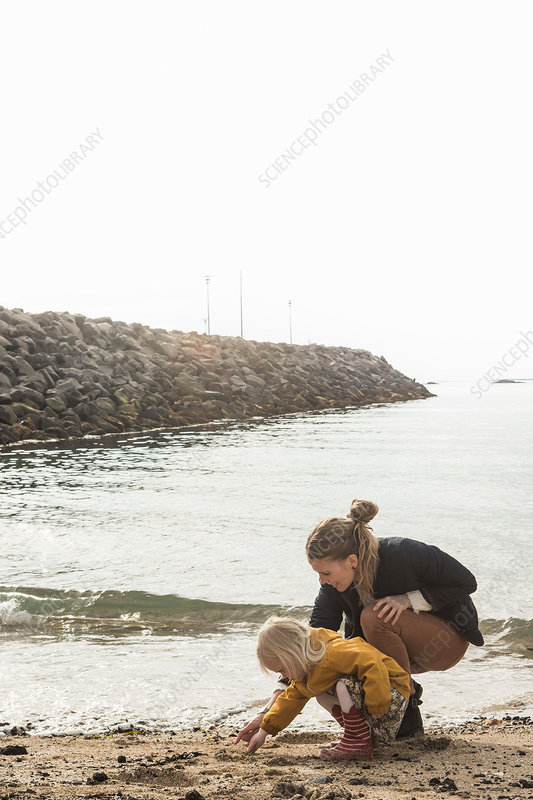 Mother and toddler exploring shoreline