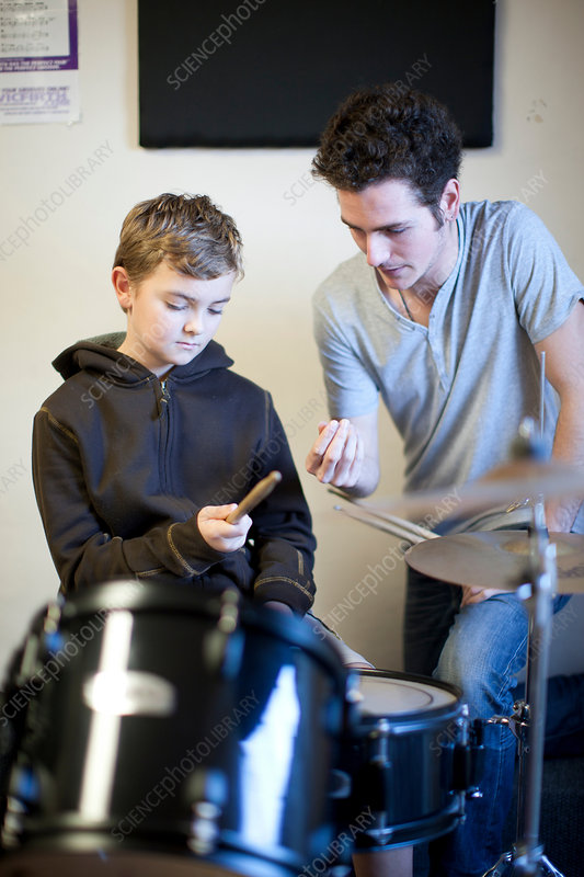 Male teaching boy how to hold drumsticks