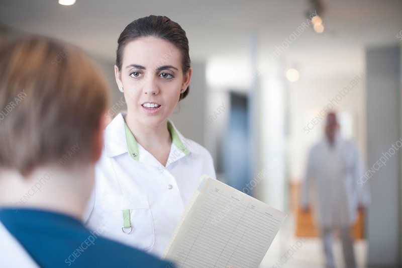 Nurse with patient and notes in reception