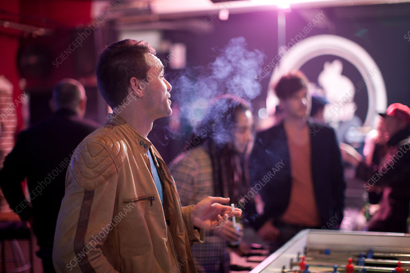 Man smoking cigarette in bar