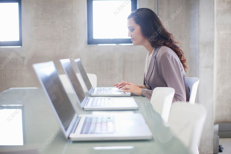 Woman and row of laptops in boardroom