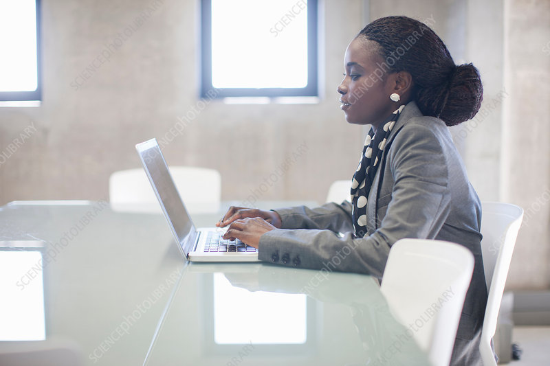 Young woman using laptop in boardroom
