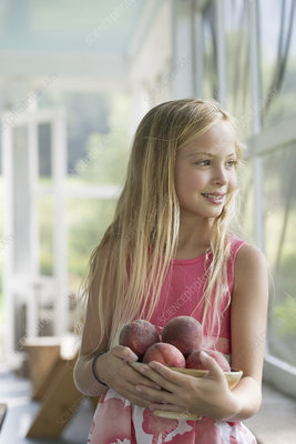 A young girl carrying fresh peaches