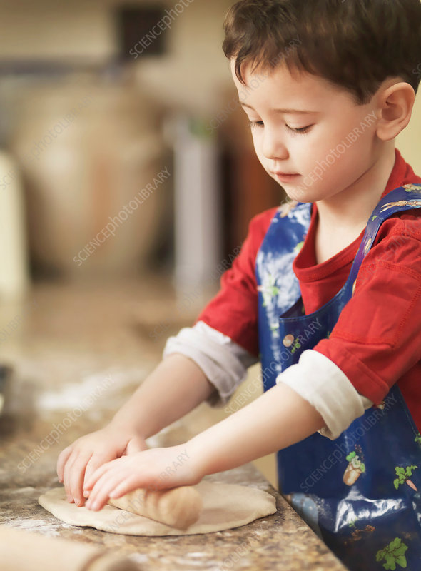 Child kneading dough with rolling pin
