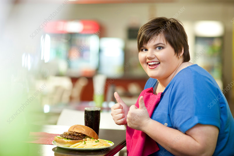 Young woman in cafe with unhealthy meal