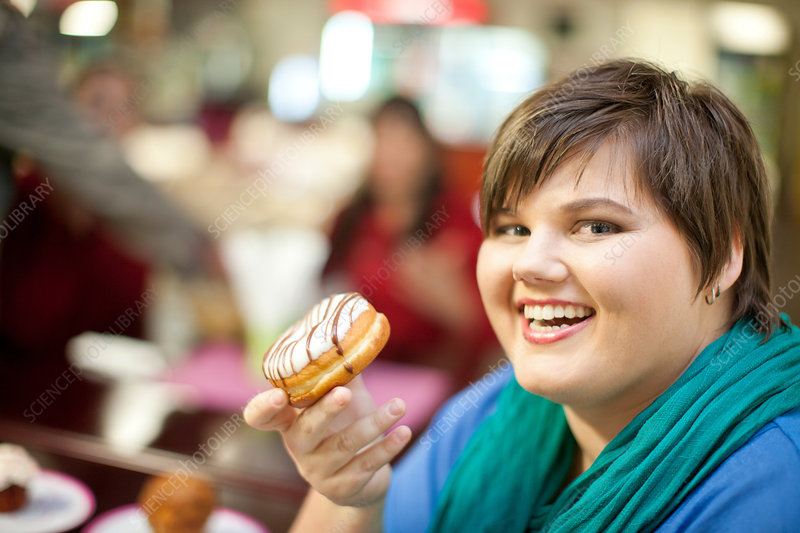 Portrait of young woman holding doughnut