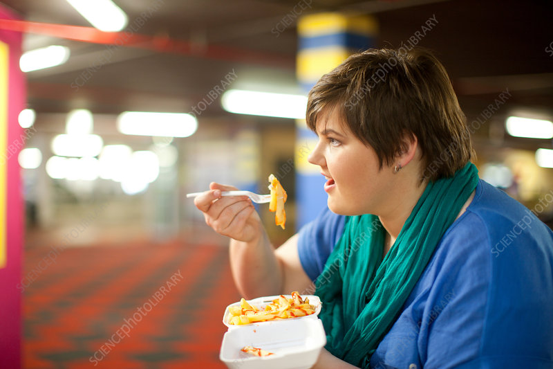 Young woman eating takeaway fries