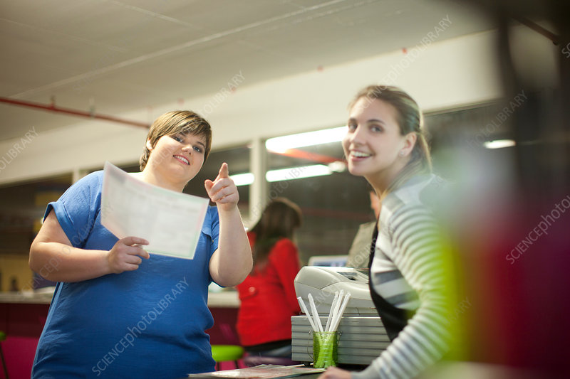 Young woman ordering from menu in cafe