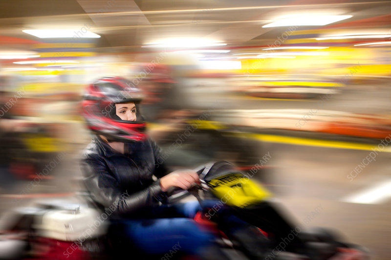 Teenage girl driving go cart on track