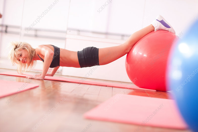 Woman in gym training with exercise balls