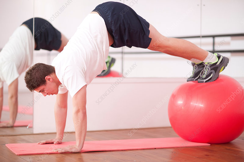 Young man training with exercise ball