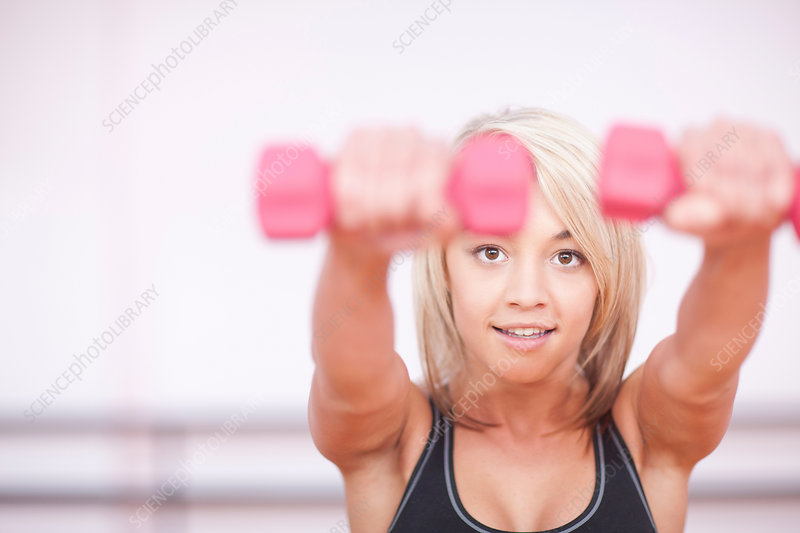Woman training with dumbbells in gym