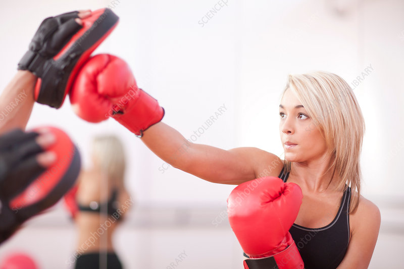 Young woman training in boxing gloves