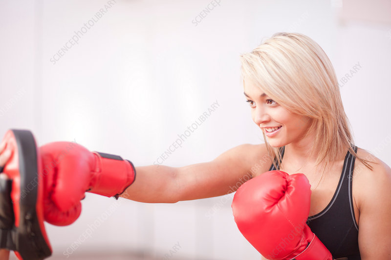 Young female training in boxing gloves