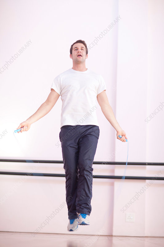 Young male skipping in gym