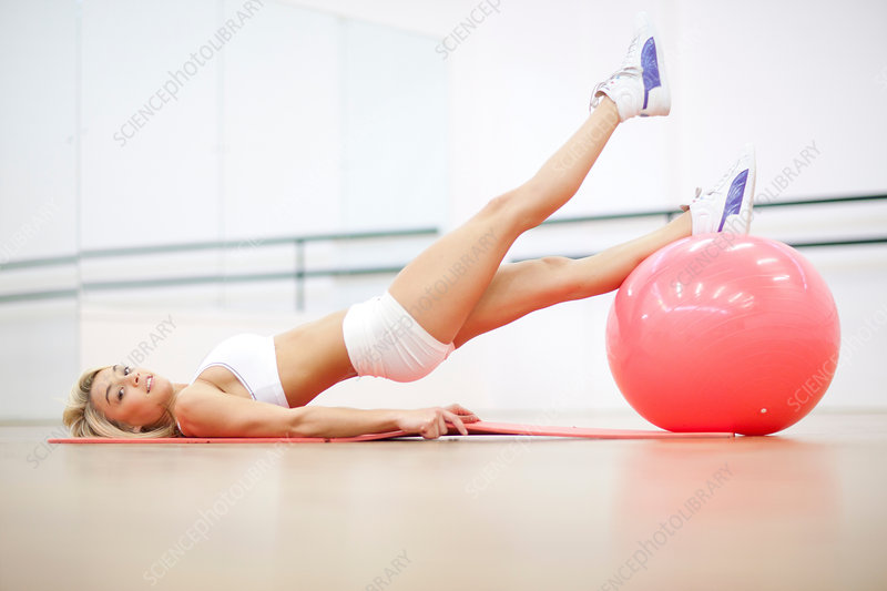 Woman in gym training with exercise ball