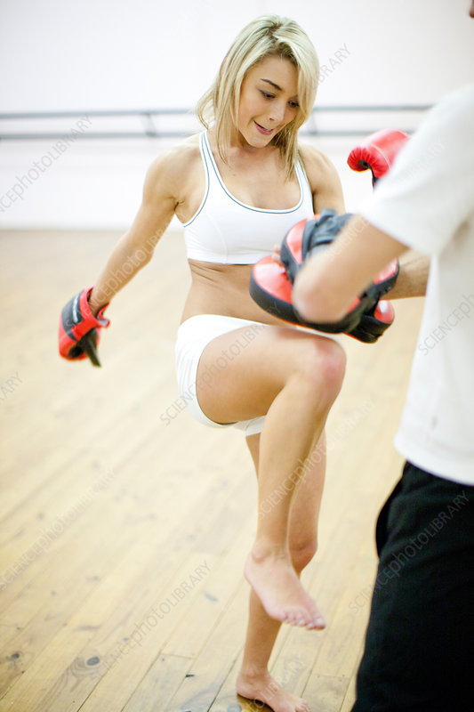 Woman kickboxing with personal trainer