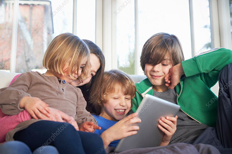 Siblings using digital tablet together