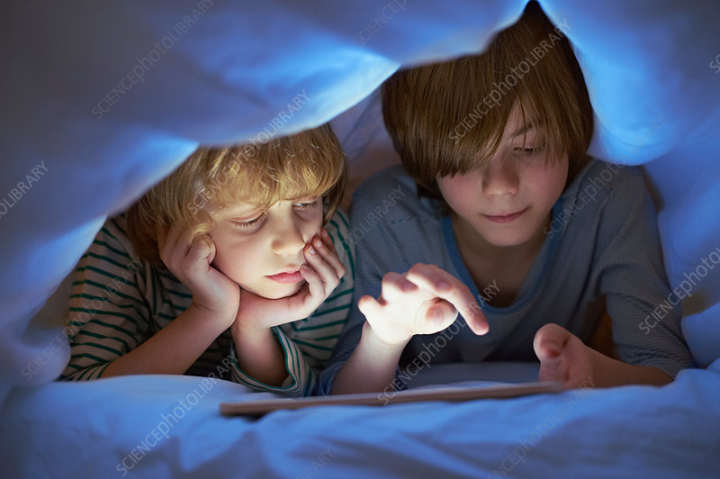 Brothers underneath duvet using tablet