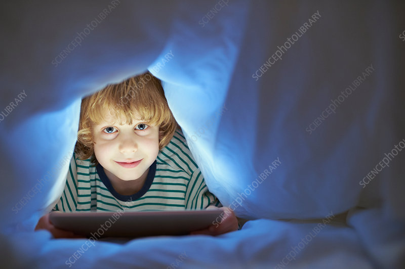 Boy underneath duvet using digital tablet