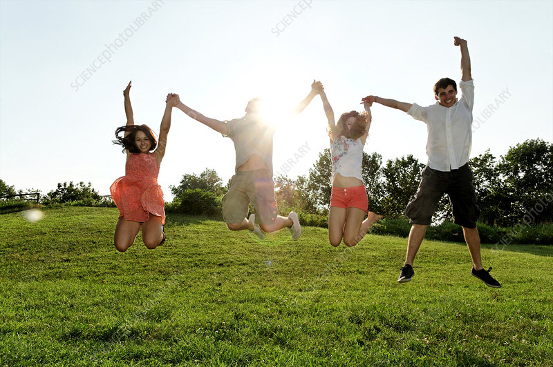 Group of young adults jumping in field