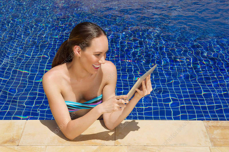 Woman using digital tablet in pool