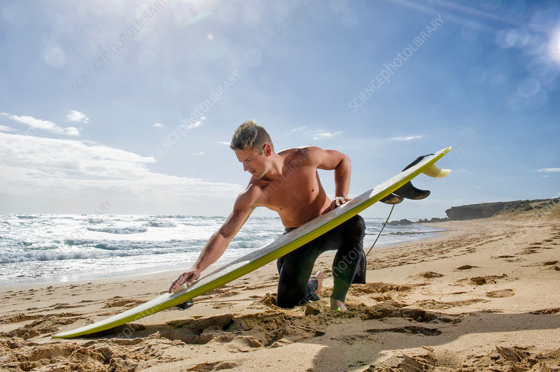 Surfer preparing surf board on beach
