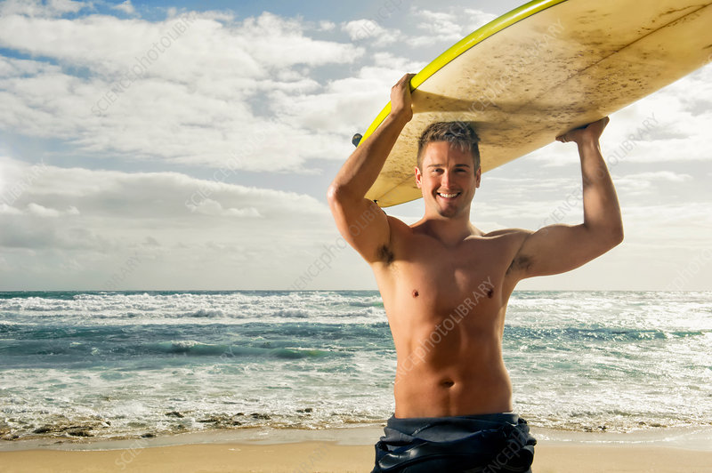 Surfer carrying surf board on head