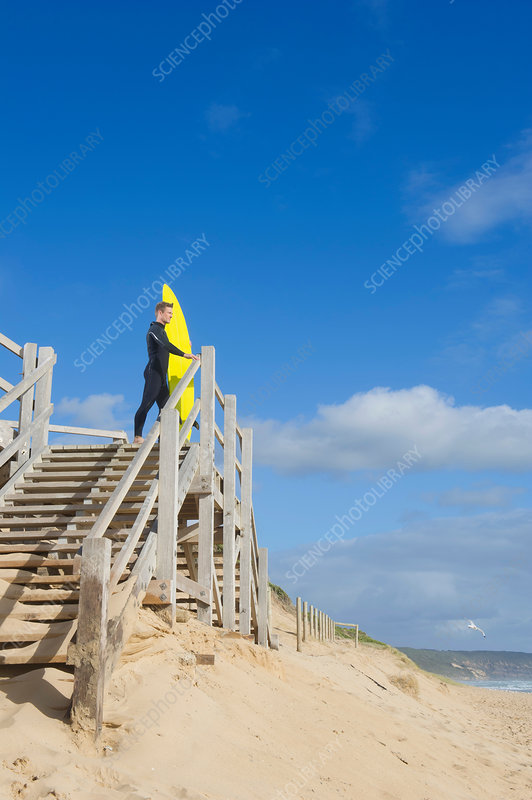 Surfer with surfboard on viewing platform