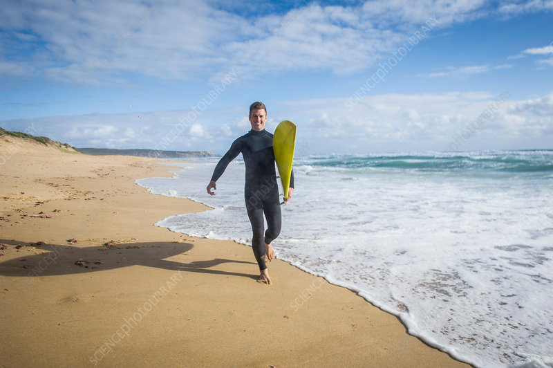 Surfer running with surfboard