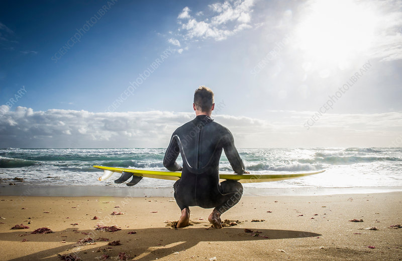 Surfer squatting with surf board