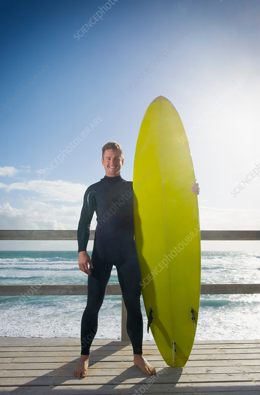 Surfer standing holding surfboard