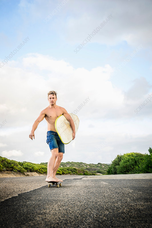 Surfer skateboarding with surfboard