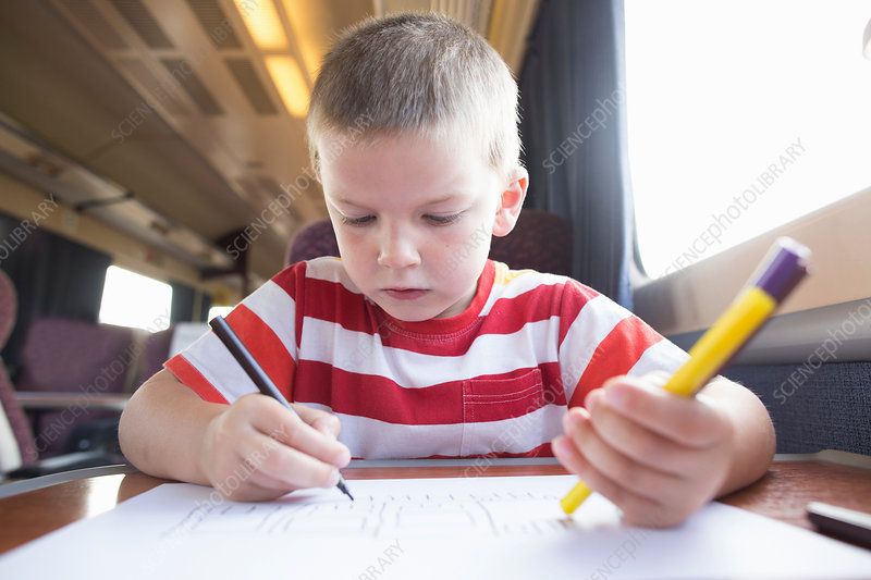 Boy with pencil, pen and paper on train