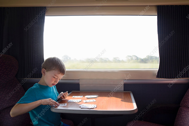 Young boy with playing cards on train