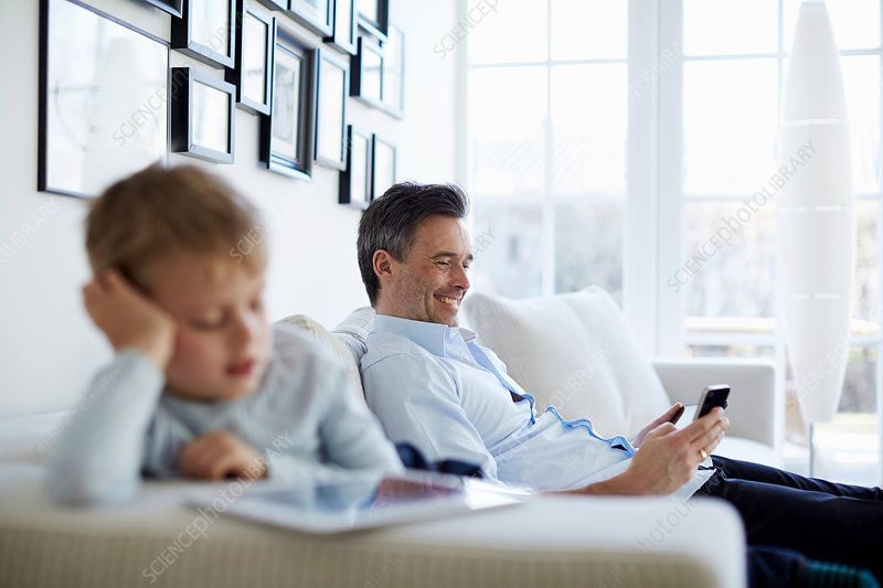 Father and son using tablet and phone