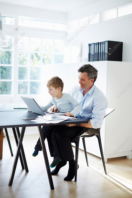 Man sitting at desk with son on his knee
