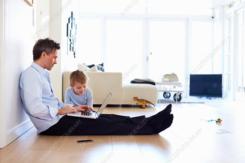 Man sitting on floor using laptop