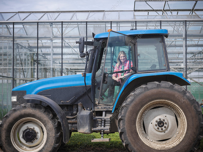 Female farmer in tractor on herb farm