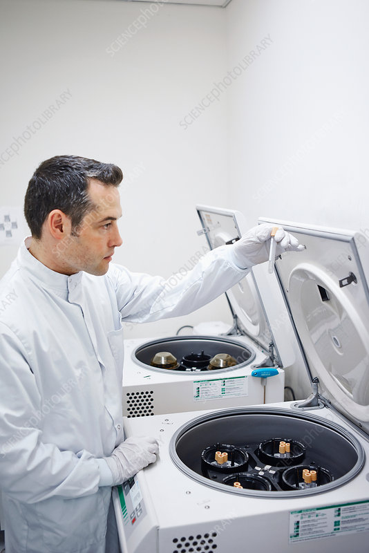 Man putting vials into centrifuge