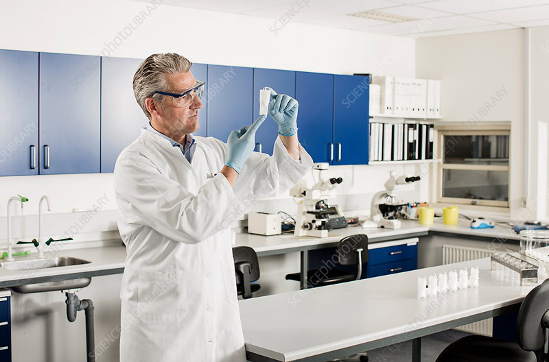 Scientist looking at container
