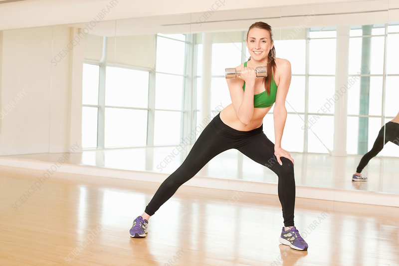 Woman stretching and lifting weights