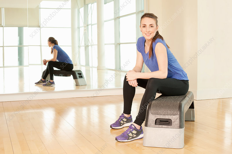 Woman sitting on step in gym