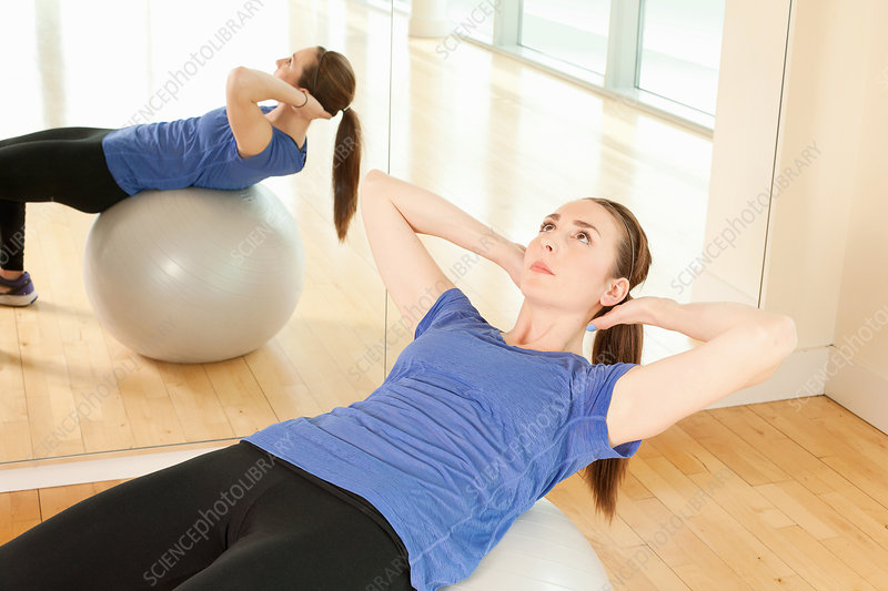 Woman on exercise ball in gymnasium