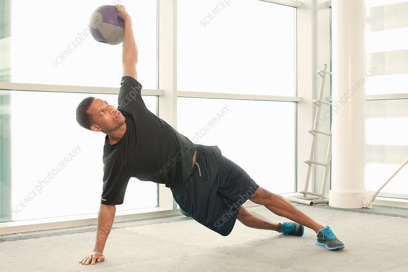 Man stretching using exercise ball