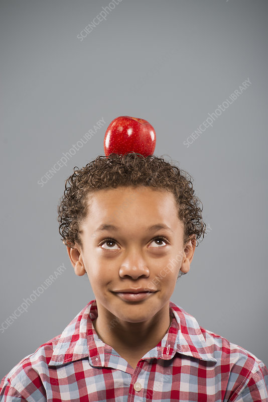 A boy with an apple on his head