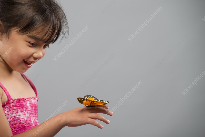 A child with a butterfly on his finger