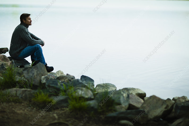 A man sitting quietly by a lake