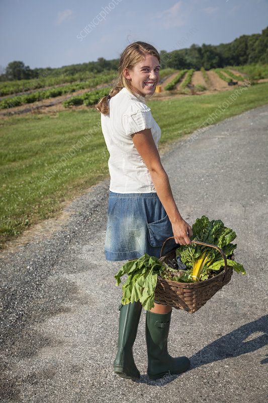 A girl in boots on a farm
