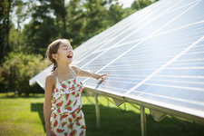 A child beside a rack of solar panels